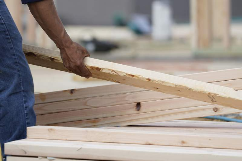 A workman arranges a beam on a frame at a new housing site in Madison County, Miss., Tuesday, March 16, 2021.   Growth in U.S. manufacturing slowed slightly in June, 2021 as supply chain problems persist and businesses say they are still struggling to find workers.(AP Photo/Rogelio V. Solis)