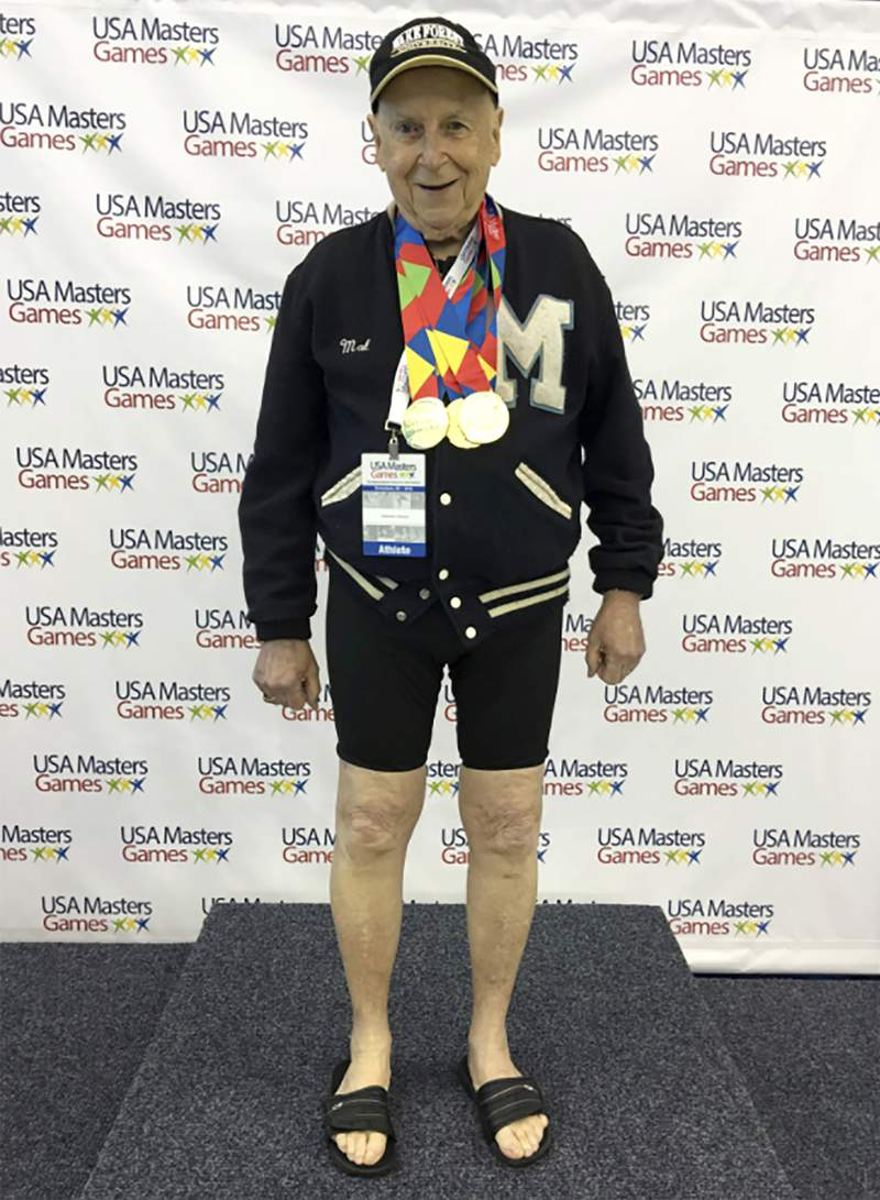 In this 2016 photo provided by Beverly Amick,  her father Mal Osborn, 92, of Winston-Salem, N.C., wears a treasured 1952 letter jacket from the University of Maine, which he earned as a track athlete, while posing at a Masters swim tournament where he won multiple gold medals. He lost the jacket in October, and with the help of a post online, it was found and returned to him. (Beverly Amick via AP)