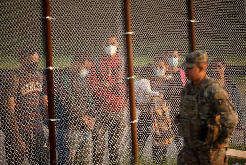 A National Guard soldier walks past a group of migrants. The group turned themselves over to Customs and Border Patrol officials at the U.S. and Mexico border in Del Rio on July 22, 2021.