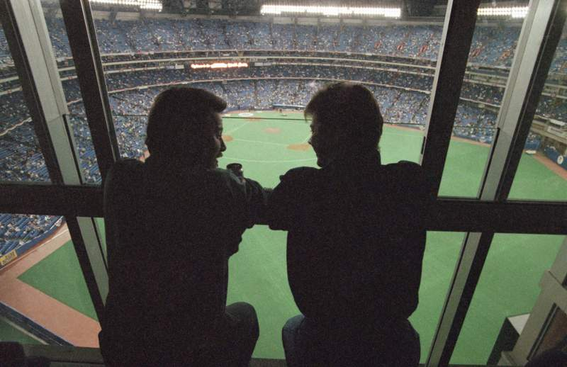 FILE - In this Oct. 22, 1992, file photo, spectators look out at the field of the SkyDome in Toronto, from a window of the SkyDome Hotel before Game 5 of the World Series between the Toronto Blue Jays and the Atlanta Braves. This week, Major League Baseball players and owners reached an agreement to play an abbreviated, 60-game season that would start July 23 or 24 in teams home ballparks. But the seats will be empty. Instead, fans hoping to see a game in person will be have to settle for pressing their faces up against hotel windows, squinting through metal grates or climb to rooftops when baseball returns this month in otherwise empty stadiums. (AP Photo/Rusty Kennedy, File)