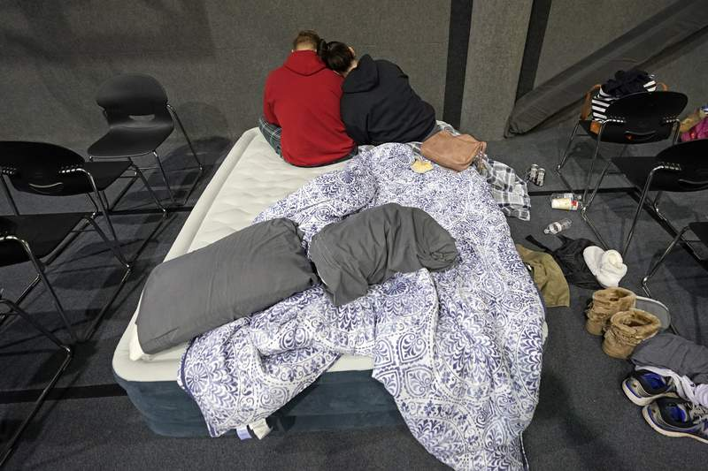 Bethany Fischer, right, rests her head on the shoulder of her husband Nic, while staying at a church warming center Tuesday, Feb. 16, 2021, in Houston. The couple, who lost power at their home on Monday, are part of the more than 4 million people in Texas who still had no power a full day after historic snowfall and single-digit temperatures created a surge of demand for electricity to warm up homes unaccustomed to such extreme lows, buckling the state's power grid and causing widespread blackouts. (AP Photo/David J. Phillip)