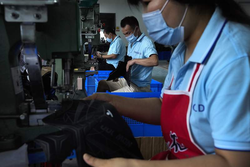 FILE - In this  July 15, 2021, file photo, workers wearing face masks to help curb the spread of the coronavirus assembly ice-skating shoes at a manufacturing factory in the ice and snow sports equipment industry park in Zhangjiakou in northwestern China's Hebei province. Chinas factory activity decelerated in August as export demand weakened, a survey showed Tuesday, Aug. 31, 2021. The monthly purchasing managers index of the Chinese statistics bureau and an official industry group declined to 50.1 from Julys 50.4 on a 100-point scale on which numbers above 50 show activity increasing. (AP Photo/Andy Wong, File)