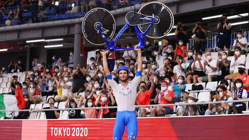 Filippo Ganna lifts his bike to celebrate after his Italian team pursuit squad set a world record to win gold Wednesday.