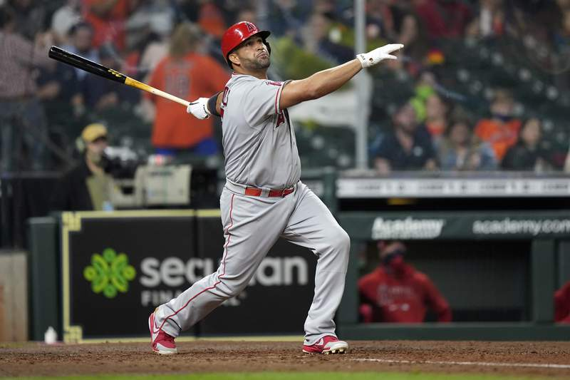 FILE - Los Angeles Angels' Albert Pujols hits a two-run home run against the Houston Astros during the sixth inning of a baseball game in Houston, in this Thursday, April 22, 2021, file photo. Pujols has been designated for assignment by the Los Angeles Angels, abruptly ending the 41-year-old superstar slugger's decade with his second major league team. The Angels announced the move Thursday, May 6, 2021, a day after Pujols wasn't in their lineup for their fourth consecutive loss.  (AP Photo/David J. Phillip, File)