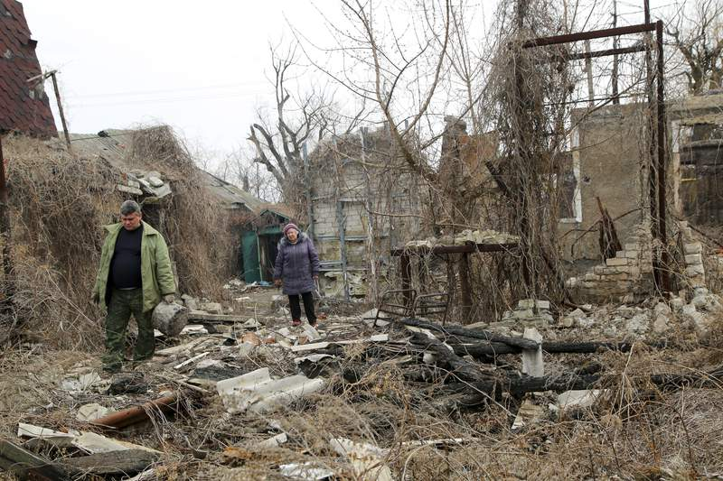 Local citizens visit their home in the separatist-controlled territory to collect belongings after a recent shelling near a frontline outside Donetsk, eastern Ukraine, Friday, April 9, 2021 .Tensions have built up in recent weeks in the area of the separatist conflict in eastern Ukraine, with violations of a cease-fire becoming increasingly frequent. (AP Photo)