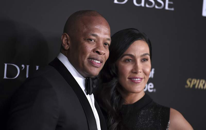FILE - In a Thursday, Oct. 11, 2018 file photo, Dr. Dre, left, and Nicole Young arrive at the City of Hope Gala, at the Barker Hangar in Santa Monica, Calif. Dr. Dres wife of 24 years Nicole Young has filed for divorce. Young filed documents Monday, June 29, 2020 seeking to end her marriage with the producer, rapper and music mogul whose real name is Andre Young in Los Angeles Superior Court.(Photo by Jordan Strauss/Invision/AP, File)