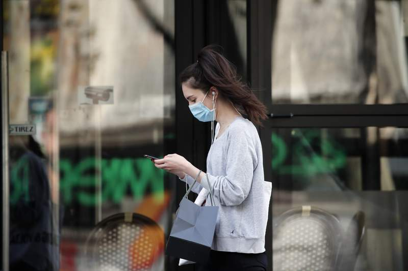 A woman wearing protective face mask walks looking at her phone past a closed restaurant during a nationwide confinement to counter the COVID-19, in Paris, Monday, April 20, 2020. A flood of new research suggests that far more people have had the Covid-19 without any symptoms, fueling hope that it will turn out to be much less lethal than originally feared. (AP Photo/Francois Mori)