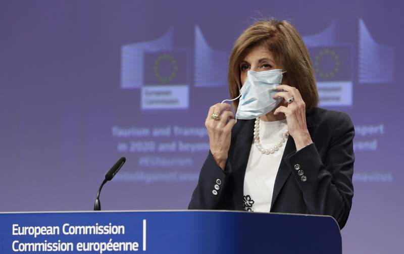 European Commissioner for Health Stella Kyriakides removes a mouth mask after addressing a media conference regarding tourism at EU headquarters in Brussels, Wednesday, May 13, 2020. The European Union unveiled Wednesday its plan to help citizens across the 27 nations salvage their summer vacations after months of coronavirus lockdown, and to resurrect Europe's badly battered tourism industry. (Olivier Hoslet, Pool Photo via AP)