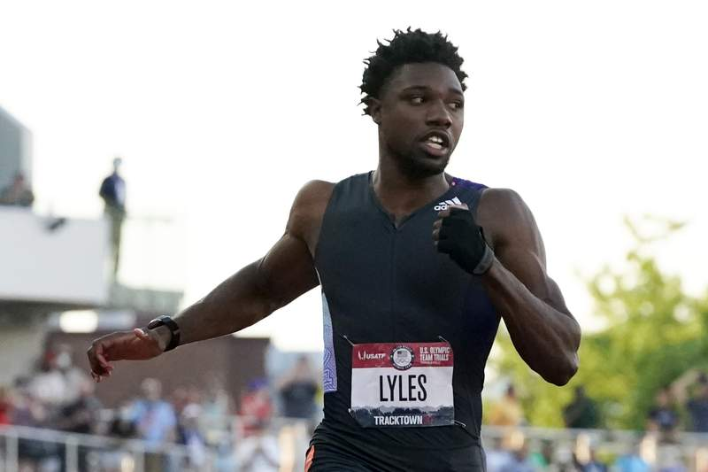 Noah Lyles competes in the second semi-final of the men's 100-meter run at the U.S. Olympic Track and Field Trials Sunday, June 20, 2021, in Eugene, Ore. In first notable demonstration of the track trials, Lyles made a subtle gesture, wearing a black glove  minus the fingers on his left hand, and raising his fist when he was introduced before the race. (AP Photo/Ashley Landis)
