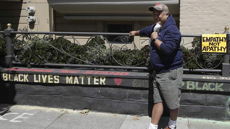 """James Juanillo poses next to chalk written outside of his home in San Francisco, Sunday, June 14, 2020. The CEO of a cosmetic company issued an apology Sunday after she and her husband confronted Juanillo and threatened to call police because he stenciled """"Black Lives Matter"""" in chalk on his San Francisco property, as the couple asserted that they know Juanillo doesn't live there and is therefore breaking the law. (AP Photo/Jeff Chiu)"""