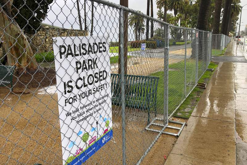 FILE - This April 9, 2020, file photo shows Palisades Park along Ocean Boulevard in Santa Monica, Calif., closed and fenced off as the city takes steps to limit public access to beaches and parks amid efforts to control the coronavirus pandemic. If Gov. Gavin Newsom's so-called roadmap to ease coronavirus restrictions hinted at a return to a normal Californians could appreciate - a summer trip in the car - it quickly became apparent they wouldn't be leaving home soon. The governor's sobering message foreshadows a summer without baseball games under the lights, large outdoor concerts, rides at amusement parks or trips to the beach. In short: a summer bummer. (AP Photo/Reed Saxon, File)