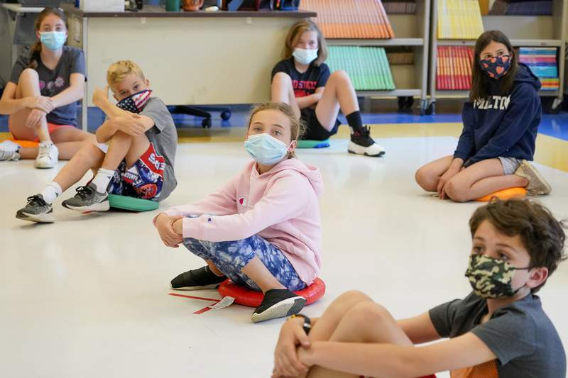 FILE - In this May 18, 2021 file photo, fifth graders wearing face masks are seated at proper social distancing during a music class at the Milton Elementary School in Rye, N.Y. As the nation closes out a school year marred by the pandemic, some states are now starting to release new standardized test scores that offer an early glimpse at just how far students have fallen behind  with some states reporting that the turbulent year has reversed years of progress across every academic subject. New York, Georgia and some other states pushed to cancel testing for a second year so schools could focus on classroom learning. (AP Photo/Mary Altaffer, File)