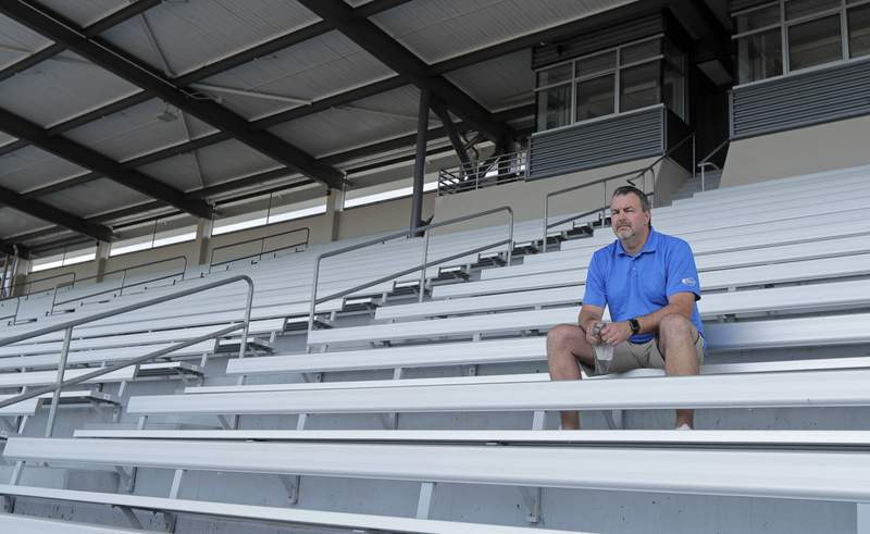 Mick Hoffman, executive director of the Washington Interscholastic Activities Association, poses for a photo, Thursday, July 16, 2020, sitting in the empty stands of the Renton School District's Renton Memorial Stadium, which is used for high school football, soccer, and track events in Renton, Wash. Hoffman and other administrators across the country are facing difficult decisions regarding the overwhelming uncertainty of whether high school sports can go forward this fall as the clock ticks closer to the start of the 2020-21 school year with little clarity in place for an obvious and safe path moving forward for athletics. (AP Photo/Ted S. Warren)