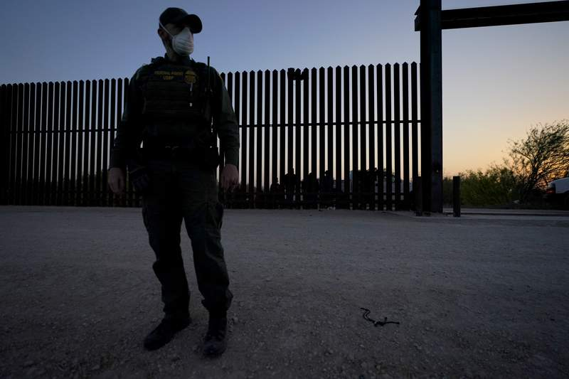 FILE - In this March 21, 2021 file photo, a U.S. Customs and Border Protection agent looks on near a gate on the U.S.-Mexico border wall as agents take migrants into custody, in Abram-Perezville, Texas. Texas Gov. Greg Abbott has has offered scarce details on his plans to construct new barrier along the border with Mexico. It remained unclear Friday, June 11 on how much barrier Texas would erect or where or when it would be installed on the state's 1,200-mile border with Mexico.  (AP Photo/Julio Cortez, File)