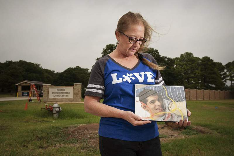Stephanie Kirby holds a photo of her son Petre Kirby outside of the Denton State Supported Living Center, where her son is a resident. She hasn't seen him since March because of COVID-19.                    Credit: Ben Torres for The Texas Tribune