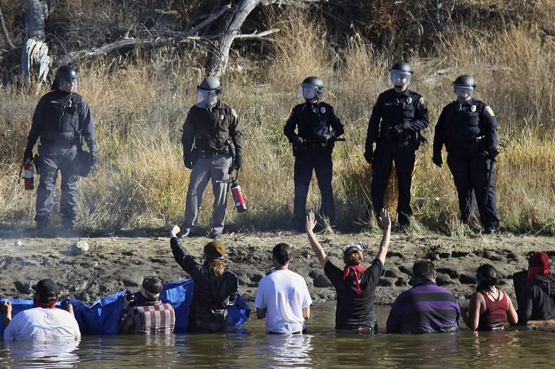 FILE - In this Nov. 2, 2016 file photo, dozens of protestors demonstrating against the expansion of the Dakota Access Pipeline wade in cold creek waters confronting local police, near Cannon Ball, N.D. The Army Corps of Engineers is recommending that the federal government negotiate a settlement with North Dakota for more than $38 million that the state spent policing the monthslong pipeline protests against the Dakota Access oil pipeline almost four years ago. (AP Photo/John L. Mone File)