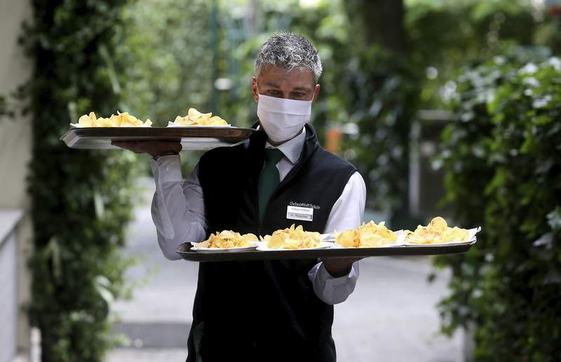 A waiter with a face mask carries food in a restaurant in Vienna, Austria, Thursday, May 14, 2020. In Austria restaurants may open again under certain conditions from Friday on. The Austrian government has moved to restrict freedom of movement for people, in an effort to slow the onset of the COVID-19 coronavirus. (AP Photo/Ronald Zak)