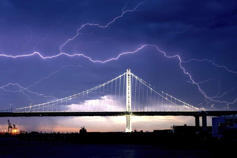 Lightning forks over the San Francisco-Oakland Bay Bridge as a storm passes over Oakland, Calif., Sunday, Aug. 16, 2020. Numerous lightning strikes early Sunday sparked brush fires throughout the region. (AP Photo/Noah Berger)