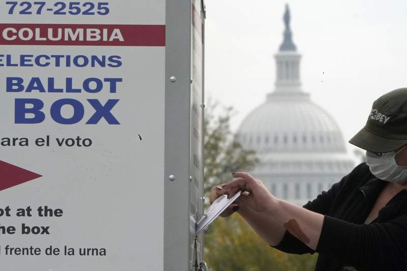 With the U.S. Capitol dome visible, a voter drops a ballot into an early voting drop box, Wednesday, Oct. 28, 2020, at Union Market in Washington. (AP Photo/Patrick Semansky)