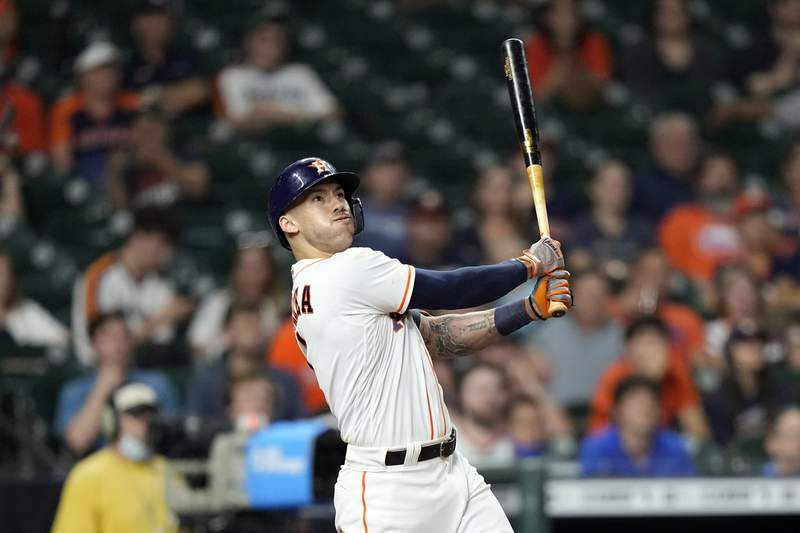Houston Astros' Carlos Correa hits a home run against the Texas Rangers during the ninth inning of a baseball game Tuesday, June 15, 2021, in Houston. (AP Photo/David J. Phillip)