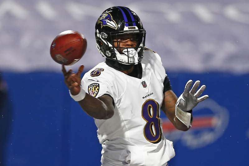 FILE - In this Jan. 16, 2021, file photo, Baltimore Ravens quarterback Lamar Jackson throws a pass during the first half of an NFL divisional round football game against the Buffalo Bills in Orchard Park, N.Y. The Ravens have exercised the fifth-year option for Jackson, the team announced Friday, April 30, 2021. (AP Photo/John Munson, File)