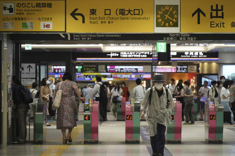 Passengers pass through the gates of a subway station in Tokyo, Friday, Aug. 6, 2021. A man stabbed four passengers with a knife on a Tokyo subway on Friday and was arrested by police after fleeing, a railway official and news reports said. (AP Photo/Kantaro Komiya)