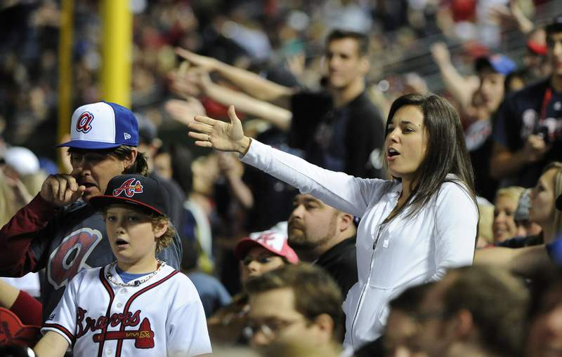 """FILE - In this May 2, 2014, file photo, Atlanta Braves fans do the tomahawk chop during the ninth inning of a baseball game with the San Francisco Giants, in Atlanta. The Atlanta Braves say they have no plans to follow the lead of the NFL's Washington Redskins and change their team name. The team said in a letter to season ticket holders they are examining the fan experience, including the tomahawk chop chant, and have formed a """"cultural working relationship"""" with the Eastern Band of the Cherokees in North Carolina. (AP Photo/David Tulis, File)"""