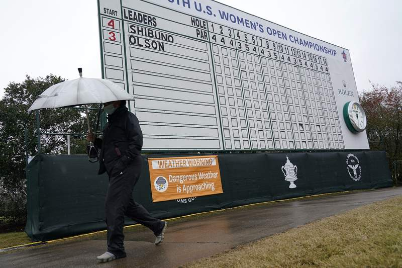 A person carries an umbrella while walking next to a sign advising that play is temporarily suspended during a weather delay in the final round of the U.S. Women's Open golf tournament, Sunday, Dec. 13, 2020, in Houston. (AP Photo/David J. Phillip)