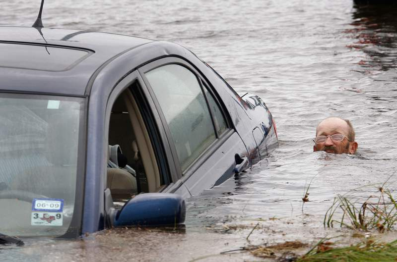 GALVESTON, TX - SEPTEMBER 12:  A man tries to rescue a car that was swept away by flood water caused by Hurricane Ike while trying to evacuate Galveston Island September 12, 2008 in Galveston, Texas. The eye of the hurricane is expected to make landfall at Galveston Island early Saturday morning.  (Photo by Scott Olson/Getty Images)