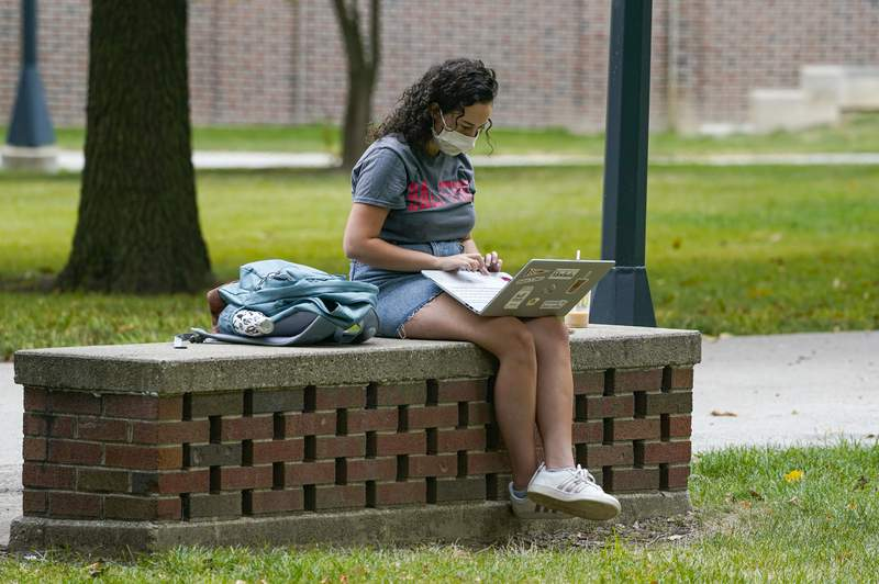A masked student works on her laptop on the campus of Ball State University in Muncie, Ind., Thursday, Sept. 10, 2020. (AP Photo/Michael Conroy)