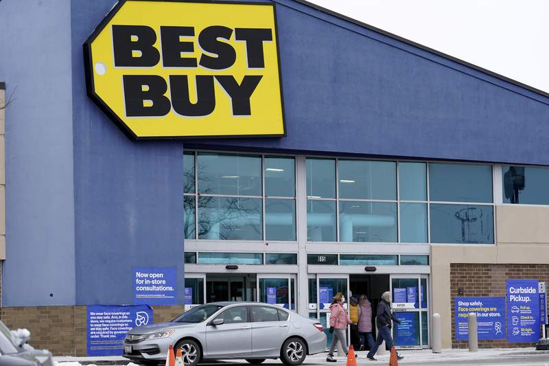 FILE - Shoppers enter and exit a Best Buy store in Arlington Heights, Ill., Saturday, Feb. 6, 2021. Best Buy Co. is raising its full-year sales outlook after the nations largest consumer electronics chain posted fiscal second-quarter results that beat analysts projections. Best Buy joins a slew of other retailers including Walmart, Target  and Macys that have posted strong results for the quarter, underscoring that the consumer remains resilient. (AP Photo/Nam Y. Huh, file)