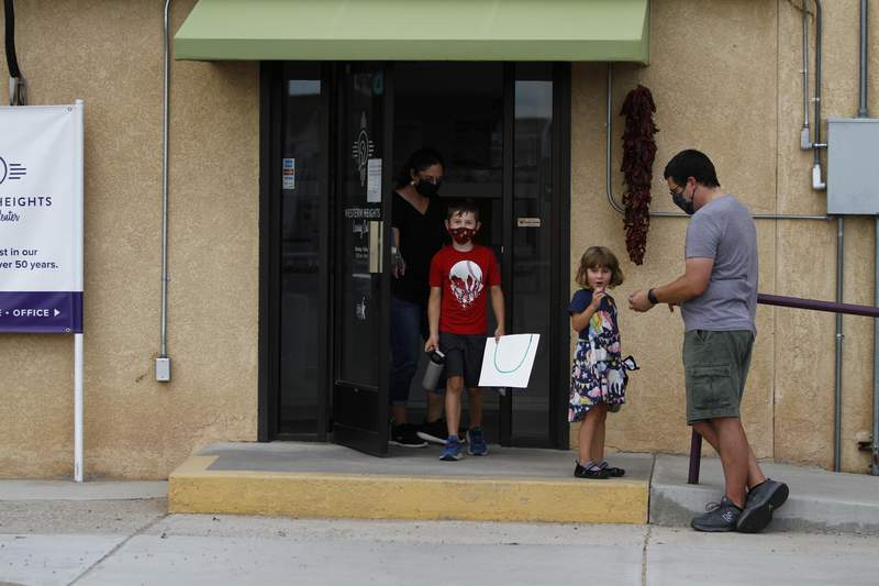 Public elementary school teachers Julia and Seth Hooper pick up their children Emry, 7, and Ivy, 4, on Monday, Aug. 10, at the Western Heights Learning Center in Albuquerque, New Mexico. The Hoopers said Emry will attend a private school at the center this fall because public schools won't be in person. Emry struggled with online learning in the spring and his parents were unable to help him while simultaneously teaching other online classes. (AP Photo/Cedar Attanasio)