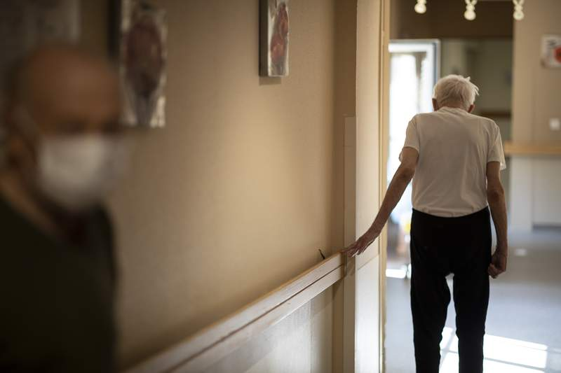 FILE - In this April 16, 2020, file photo, Richard Eberhardt walks along a corridor at a nursing home in Kaysesberg, France. Countries across Europe are struggling amid the coronavirus pandemic with the dilemma of leaving the elderly and others near death in enforced solitude or whether to allow some personal contact with relatives. At nursing homes, everything is done to keep out visitors who might be infected, and family members are almost always banned from coming to see their loved ones. (AP Photo/Jean-Francois Badias, File)