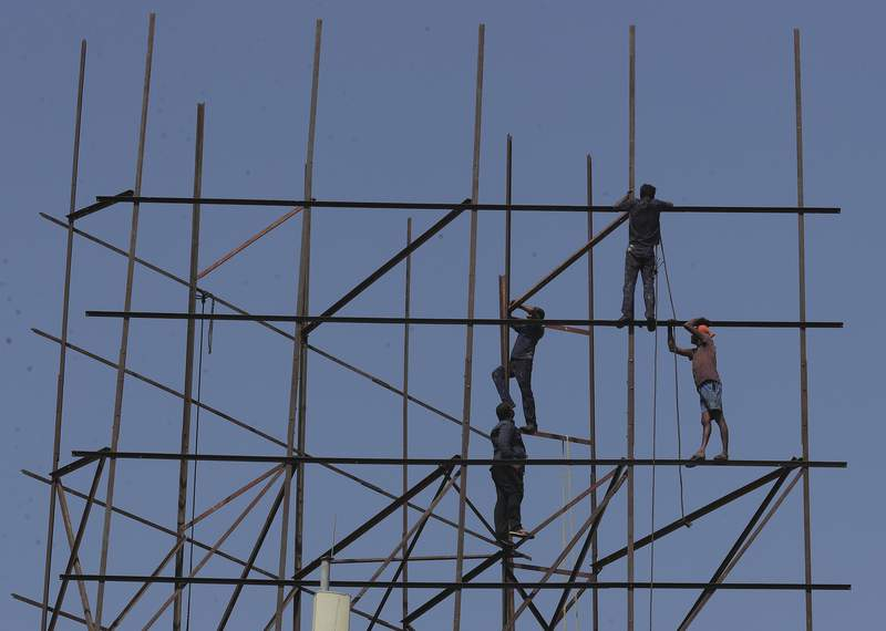 Indian workers repair an advertising hoarding in Hyderabad, India, Tuesday, Jan. 21, 2020. The IMF on Monday lowered Indias economic growth estimate for the current fiscal to 4.8% and listed the countrys Gross Domestic Product (GDP) numbers as the single biggest drag on its global growth forecast for two years. (AP Photo/Mahesh Kumar A.)