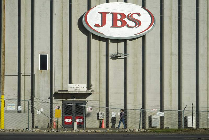 FILE - In this Oct. 12, 2020 file photo, a worker heads into the JBS meatpacking plant in Greeley, Colo. The worlds largest meat processing company says it paid the equivalent of $11 million to hackers who broke into its computer system late last month. Brazil-based JBS SA said on May 31 that it was the victim of a ransomware attack, but Wednesday, June 9, 2021 was the first time the companys U.S. division confirmed that it had paid the ransom. (AP Photo/David Zalubowski, File)