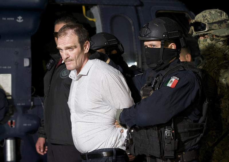 """FILE - In this June 15, 2016 file photo provided by the Mexican Attorney General's Office, Hector """"El Guero"""" Palma, or Blondie, one of the founders of the Sinaloa Cartel, is escorted in handcuffs from a helicopter at a federal hangar in Mexico City, after serving almost a decade in a U.S. prison and transported to another maximum-security lockup to await trial for two murders. (Mexico's Attorney General's Office via AP, File)"""
