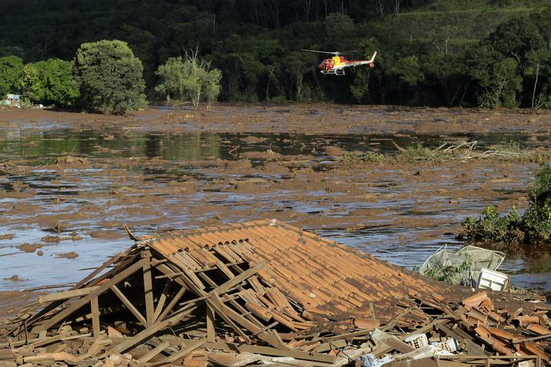 FILE - In this Jan. 27, 2019 file photo, rescue workers in a helicopter search a flooded area after a dam collapsed in Brumadinho, Brazil. Brazilian mining giant Vale signed a settlement deal on Thursday, Feb. 4, 2021, to pay 37.7 billion reais ($7 billion) to the state of Minas Gerais, following the collapse of a dam two years ago that devastated the city of Brumadinho and killed at least 272 people. (AP Photo/Andre Penner, File)
