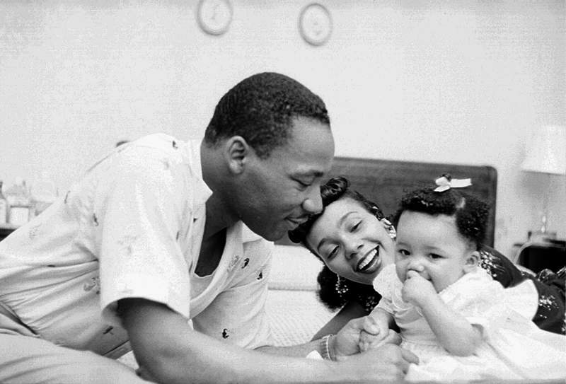 Martin Luther King, Jr. relaxes at home with his family in May 1956 in Montgomery, Alabama with his newborn baby and wife.