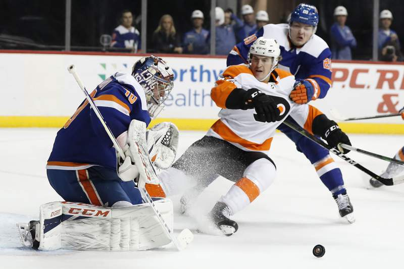 FILE - In This Feb. 11, 2020, file photo, New York Islanders goaltender Semyon Varlamov (40) deflects the puck as Islanders left wing Kieffer Bellows (20) keeps Philadelphia Flyers right wing Nicolas Aube-Kubel (62) away during the first period of an NHL hockey game in New York. The NHL ditched divisional playoffs to go back to the old-school format for its summer postseason and still ended up with all division rivals facing off in the second round. Its the Flyers against Islanders in the Metropolitan series. (AP Photo/Kathy Willens, File)