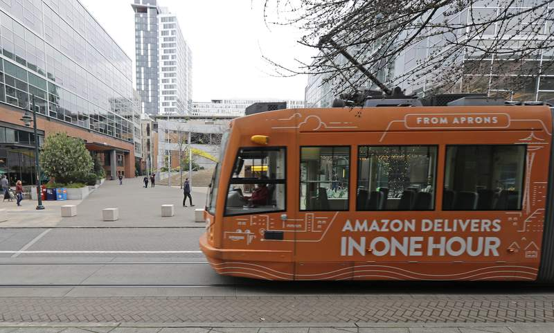 FILE - This Nov. 13, 2018 file photo a South Lake Union streetcar with an advertisement for Amazon.com's same-day delivery service passes by an Amazon office building in Seattle's South Lake Union neighborhood. Amazon has pushed back its return-to-office date for tech and corporate workers until January 2022 as COVID-19 cases surge nationally due to the delta variant. The Seattle Times reported on the tech giant's delay in returning to offices from internal messages. (AP Photo/Ted S. Warren,File)