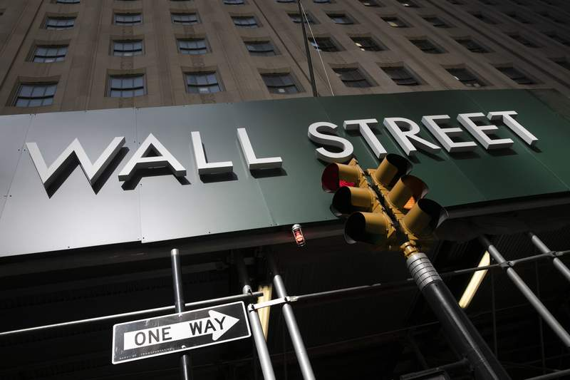 FILE -In this June 16, 2020 file photo, a sign for a Wall Street building is shown in New York.  Stocks are opening mostly lower on Wall Street Thursday, Aug. 13, a day after the S&P 500 closed just below its pre-pandemic record high. (AP Photo/Mark Lennihan, File)