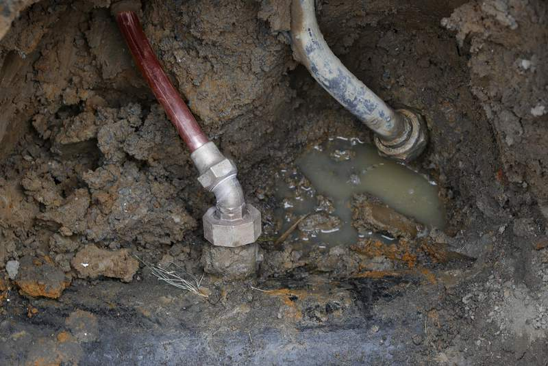 FILE - In this July 20, 2018, file photo a copper water supply line, left, is shown connected to a water main after being installed for lead pipe, right, in Flint, Mich. The Trump administration overhauled the country's widely criticized, 29-year-old framework to eliminate toxic lead from drinking water on Tuesday, but critics charge that the new rule gives utilities far more time than before to finally replace old, lead-contaminated pipes. (AP Photo/Paul Sancya, File)