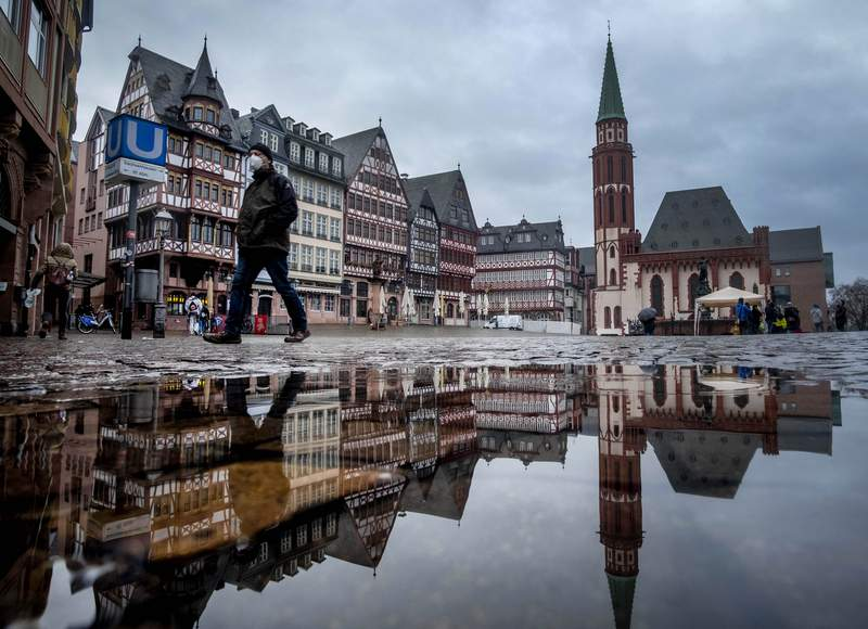 A man wears a face mask as he walks over the Roemerberg square in Frankfurt, Germany, Thursday, Jan. 28, 2021. Further restrictions to avoid the outspread of the coronavirus are discussed Thursday by the German government. (AP Photo/Michael Probst)