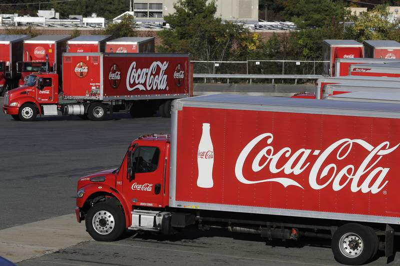 FILE - In this Oct. 14, 2019 photo a truck with the Coca-Cola logo, behind left, maneuvers in a parking lot at a bottling plant in Needham, Mass. The Coca-Cola Co. said Thursday, Dec. 17, 2020, its laying off 2,200 workers, or 17% of its global workforce, as part of a larger restructuring aimed at paring down its business units and brands. (AP Photo/Steven Senne, File)