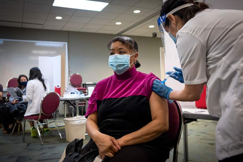 Beverly Mills, a teacher at Anderson Elementary School, gets vaccinated by pharmacist Ilana Druker at Houston Independent School Districts Hattie Mae White Educational Support Center on Jan. 9, 2020 in Houston.