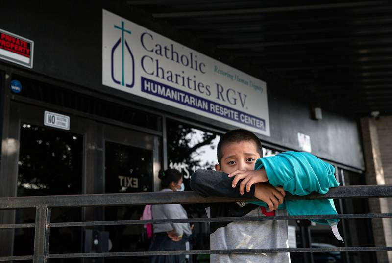 A migrant child waits with his family in front of the Catholic Charities RGV Humanitarian Respite Center in McAllen on July 27, 2021.