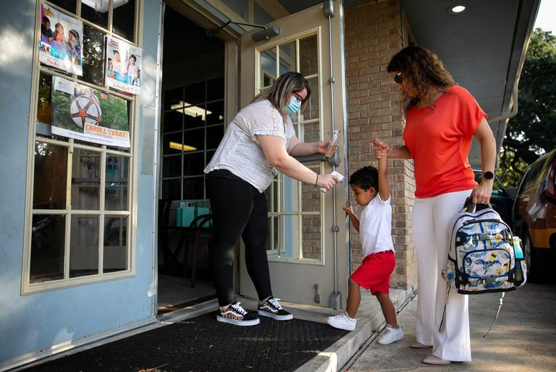 Childcare supervisor Amy Davis takes the temperature of three-year-old Nicholas as he is dropped off by his mother Melissa Hurbs at the Museum District Childcare Center in Houston on Sept. 1, 2021.