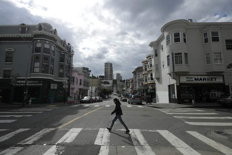 A man walks alone while crossing Green Street in the North Beach neighborhood of San Francisco, Saturday, March 21, 2020. Some 40 million Californians are coping with their first weekend under a statewide order requiring them to stay at home to help curb the spread of the coronavirus.(AP Photo/Jeff Chiu)