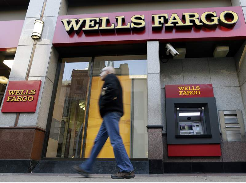 FILE - In this Wednesday, Dec. 19, 2012, file photo, a man walks past a Wells Fargo location in Philadelphia. Wells Fargo & Co. swung to a profit of $6 billion in the second quarter, after reporting a loss in the same period a year earlier. The San Francisco-based bank said Wednesday, July 14, 2021,  that it had earnings of $1.38 per share compared with a loss of $1.01 per share a year ago.(AP Photo/Matt Rourke, File)