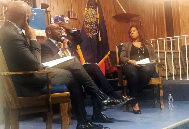 """In this Jan. 16, 2020, photo, from left, Harrison Floyd and Paris Dennard of President Donald Trump's reelection campaign black voter outreach effort and Kamilah Prince, the Republican National Committee's director of African American engagement participate in a """"Black Voices for Trump"""" event at Philadelphia's First Immanuel Baptist Church. Trump's reelection campaign is reaching out to black voters through one of their communities' most important institutions  black churches.  (AP Photo/Elana Schor)"""